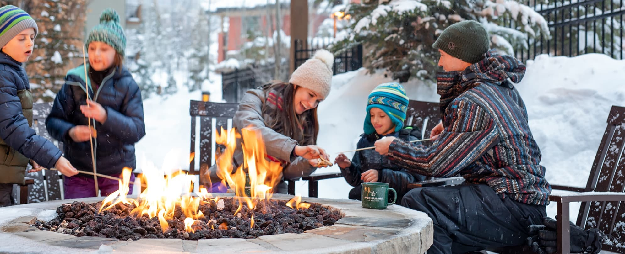 Family of five bundled up from the snow toasting marshmallows at an outdoor fire pit