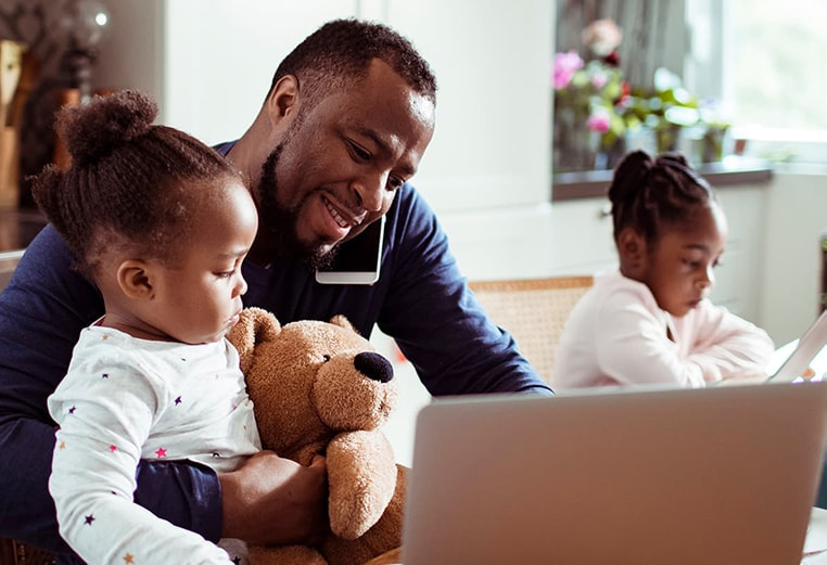 Man with his two daughters at the kitchen table, man is holding one of his daughters and her teddy bear as he talks on the phone and works on his laptop